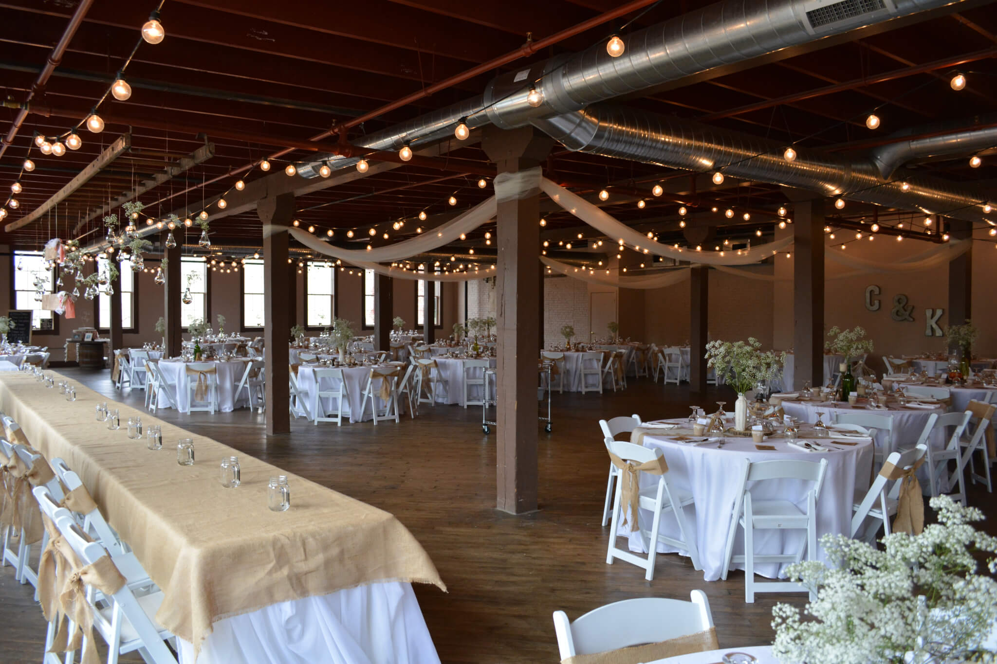 Michiana Event Venue with industrial charm, string lights, white chairs, round tables and historic ambiance