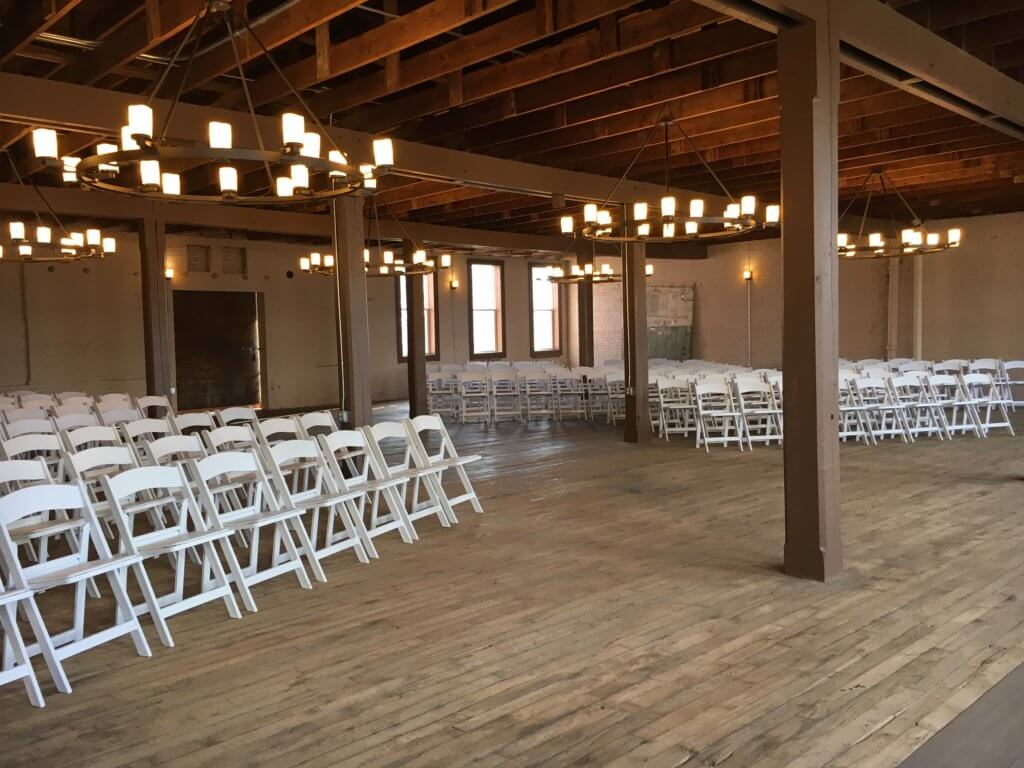 Dramatic custom candelabra chandeliers, brick walls, ambient lighting and wood floors characterize the Joining Room Event Center at Coppes Commons in Nappanee