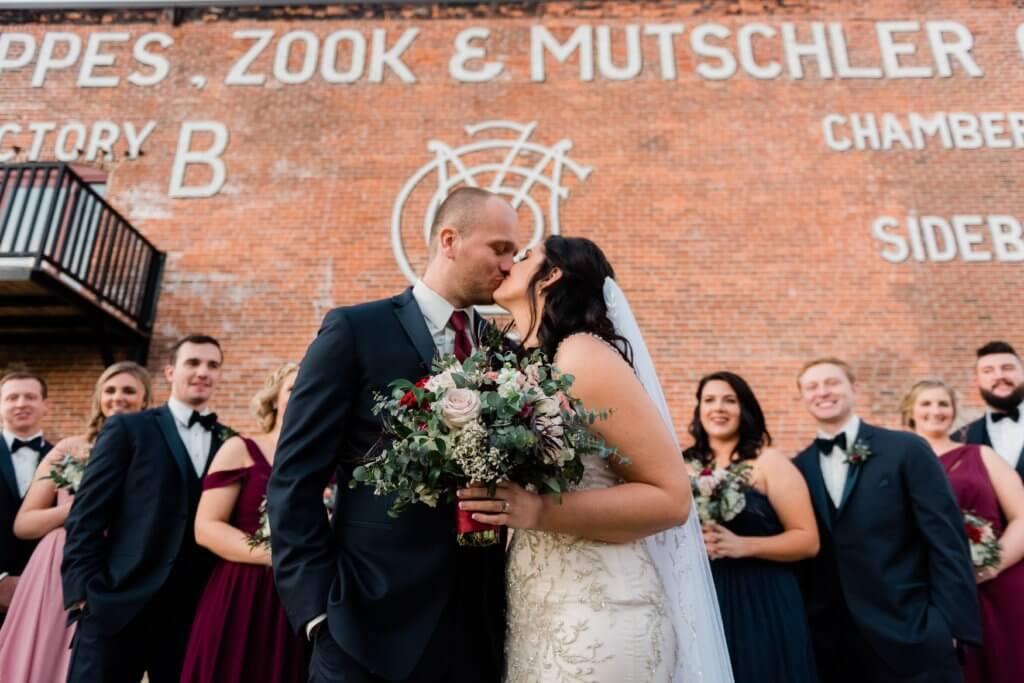 bride and groom under mural